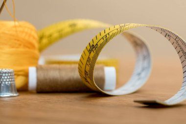 selective focus of measuring tape with thread coil on wooden table