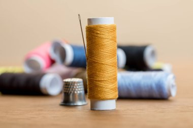 selective focus of cotton thread coil with needle isolated on beige