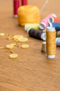 selective focus of thimble and yellow thread coil with needle on wooden table with copy space