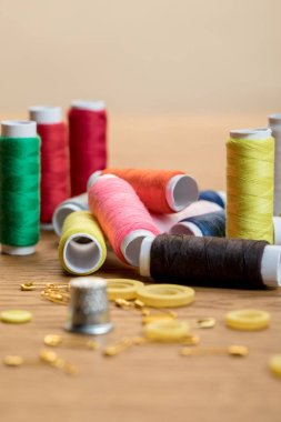 selective focus of colorful thread coils, safety pins and buttons isolated on beige