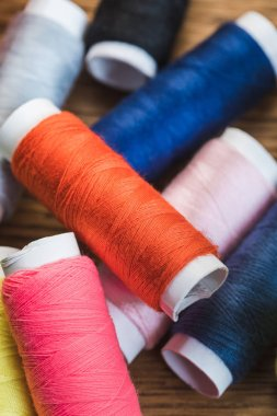 close up view of scattered colorful cotton thread coils
