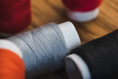 close up view of grey and black cotton thread coils