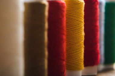 close up view of colorful cotton thread coils in row