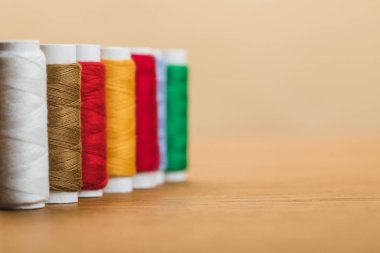 colorful cotton thread coils in row isolated on beige with copy space