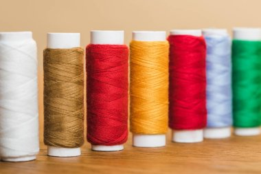 colorful cotton thread coils in row on wooden table isolated on beige