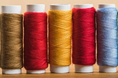 close up view of colorful cotton thread coils in row isolated on beige