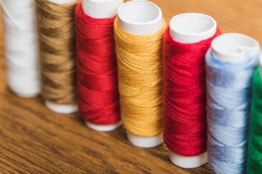 colorful cotton thread coils in row on wooden surface