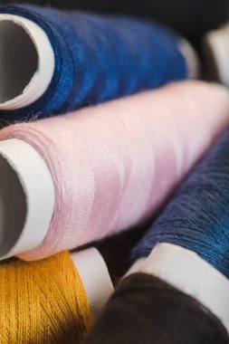 close up view of pink, blue and yellow cotton thread coils