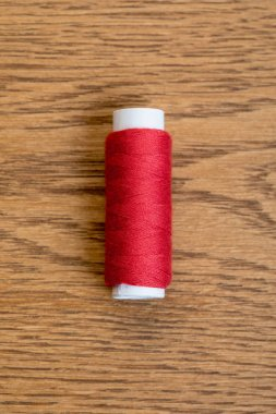 top view of red cotton thread coil on wooden surface