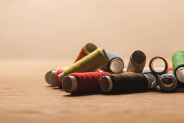 selective focus of colorful cotton thread coils on table isolated on beige