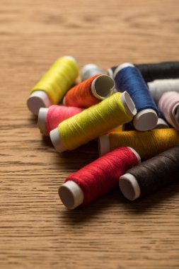 scattered colorful cotton thread coils on wooden surface
