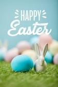 kék festett tojás közelében dekoratív nyuszi zöld fű, Boldog húsvéti betűkkel a fenti