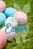 Fotografia pile of multicolored painted chicken eggs with happy Easter lettering in rabbit illustration on green grass