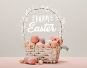 wicker basket with pink painted eggs, flowers and happy Easter lettering on grey background