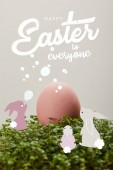 Fotografie pink painted chicken egg on green grass with happy Easter to everyone lettering and rabbits illustration
