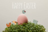 Fotografia pink painted chicken egg on green grass with happy Easter lettering and birds illustration on grey background