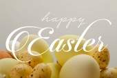 yellow painted chicken and quail eggs with happy Easter lettering on grey background