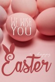 Fotografie pink painted chicken eggs with we wish you happy Easter lettering
