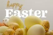 gelb bemalte Eier mit fröhlichem Osteraufdruck auf grauem Hintergrund