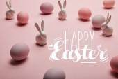 rosa bemalte Hühnereier mit dekorativen Hasen und fröhlichen Osteraufschriften