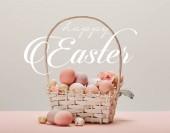 košík s růžovými malovanými vejci, květiny a šťastné velikonoční bílé nápisy na šedém pozadí