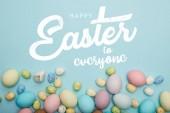 Fényképek felülnézet festett sokszínű tojás szétszórva dekoratív nyuszi kék háttér Boldog Húsvétot mindenkinek betűkkel