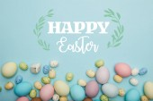 Fotografie top view of painted multicolored eggs scattered and decorative bunny on blue background with happy Easter lettering