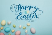 Fotografie top view of painted multicolored eggs scattered near decorative rabbit on blue background with happy Easter lettering