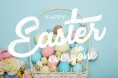 top view of painted multicolored eggs, wicker basket and flowers on blue background with happy Easter to everyone lettering