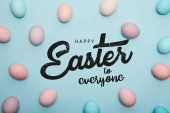 Fotografie top view of painted multicolored eggs on blue background with happy Easter to everyone lettering