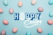 Fotografia top view of painted colorful eggs on blue background with happy Easter lettering