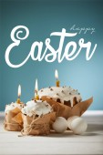 Fotografie traditional Easter cakes in craft paper with burning candles and white chicken eggs on blue background with happy easter lettering