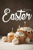 traditionelle leckere Osterkuchen mit brennenden Kerzen und weißen Hühnereiern auf braunem Hintergrund mit fröhlichem Osteraufdruck