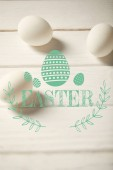 Fotografie chicken eggs on white wooden table with turquoise Easter lettering