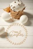 tradiční velikonoční dort a bílá Kuřecí vejce na bílém dřevěném stole s šťastným písmem na Velikonoce