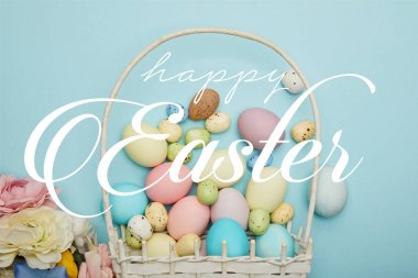 top view of painted multicolored eggs scattered near wicker basket and flowers on blue background with happy Easter lettering
