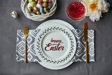 top view of festive table setting for Easter with decor and happy Easter lettering on plate