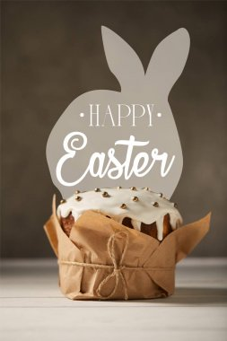 traditional decorated Easter cake in craft paper on white table with happy easter lettering and bunny illustration on brown background