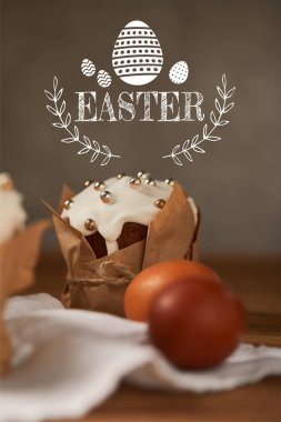 selective focus of traditional Easter cake in craft paper and chicken eggs on napkin with easter lettering
