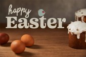 Fotografie selective focus of traditional Easter cakes and chicken eggs on wooden table with happy easter lettering and bird illustration