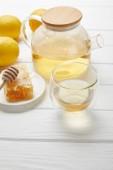 čajový hrnec s organickým bylinkovým čajem, skleněnými, citrony a medovým hřebenem na bílém dřevěném stole