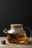 transparent teapot with blooming tea and tea balls on wooden table isolated on black with copy space