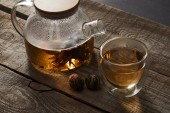 transparent teapot and glass with chinese blooming tea on wooden table