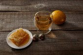 glass of traditional chinese blooming tea, lemon and honeycomb on wooden surface