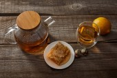 Fotografie lemon, honeycomb and transparent teapot with glass of chinese blooming tea on wooden table