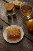 glass of traditional chinese blooming tea, lemons and honeycomb on wooden table