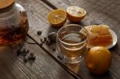 citrony, voštany a průsvitné čajové konvice se sklenicí tradičního čínského Kvetoucí čaje na dřevěném stole