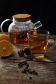átlátszó teáskanna a virágzó tea, csésze, citrom és tea golyó a fából készült asztal izolált fekete