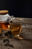 Fotografie transparent teapot and cup with traditional blooming tea on wooden table isolated on black