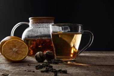 transparent teapot and cup with traditional blooming tea on wooden table with lemons isolated on black